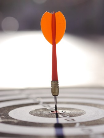 One dart is hitting perfectly on the black dart board