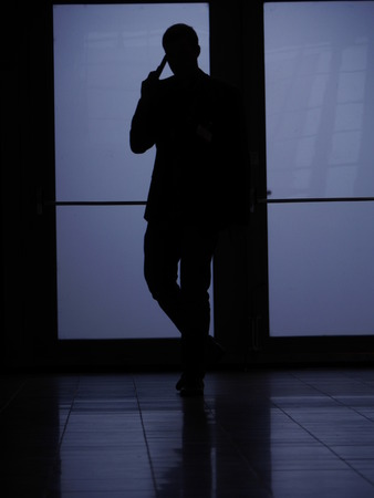the silhouette of a man who is phoning.