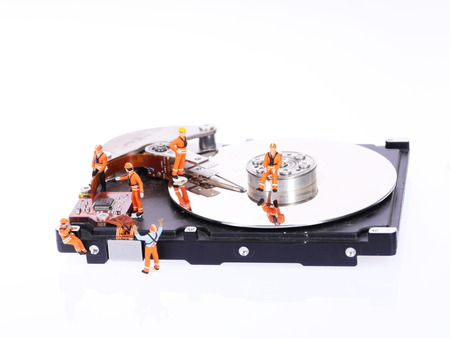 Group of miniature technicians repair hard drive photo