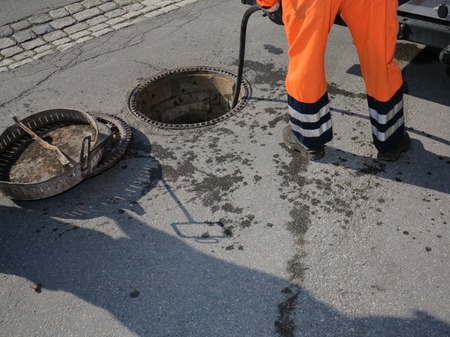 riolering werknemer op straatreiniging pijp Stockfoto