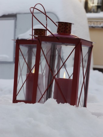 red candles on white snow outside in winter photo