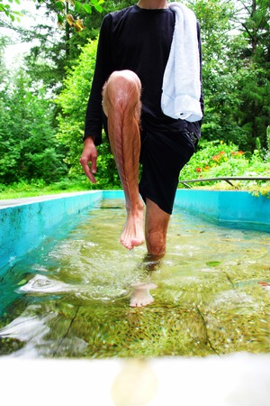 oft: Close-up of a man getting into water Stock Photo