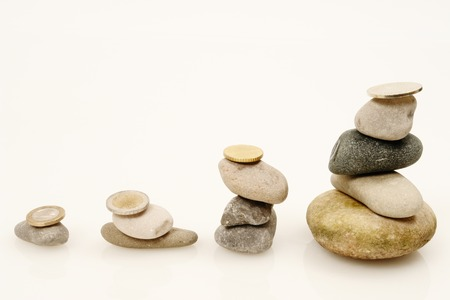 Coins and Pebbles on white as a symbol for financial balance photo