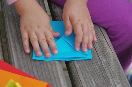 Hands of child folding with paper boats