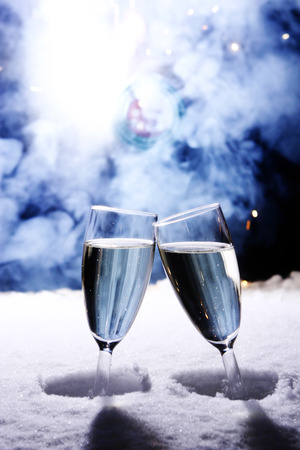 clink: two champagne glasses in snow clink glasses for new year on sylvester firework in background