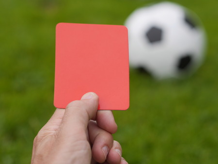 Hand holding up red card against soccer field Stock Photo