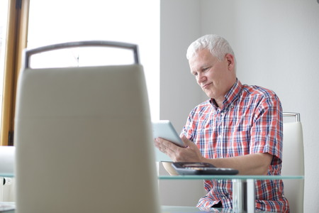 sceptical: Senior man working in a modern office on a tablet computer grimacing with a sceptical expression as he reads information on the screen
