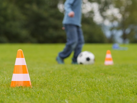traffic cones: training soccer ball on a green field Stock Photo