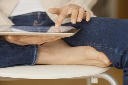 crosslegged: woman holding digital tablet sitting cross-legged and barefoot