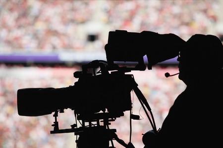 Silhoutte of a camera man in a stadium photo
