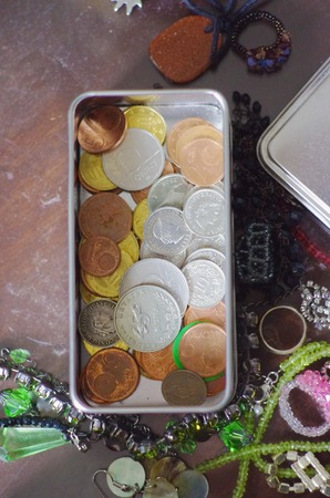 Assorted small change and coins in a tin with scattered jewellery on a tabletop, overhead view