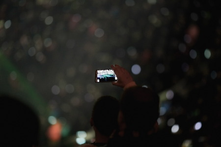 crowds of people: Hand with a smartphone in a crowd at football stadium