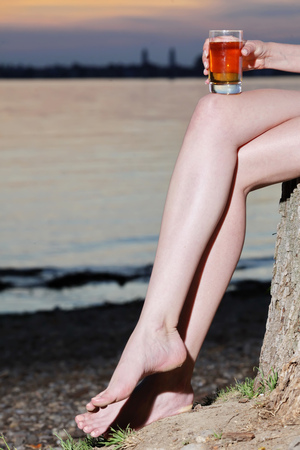 legs crossed at knee: a woman sitting on a stump with a glass in her hand Stock Photo