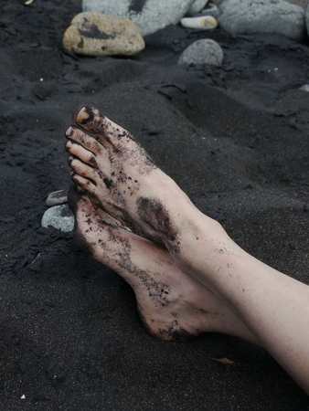maui: Mans barefeet in black sand in Maui, Hawaii.