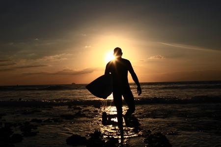 passtime: Surfer Walks Down Beach at Sunset
