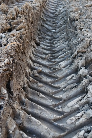 muddy tracks: deep tyre tracks in mud earth muddy