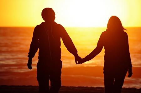 parejas enamoradas: Una pareja en la playa con el fondo del atardecer Foto de archivo