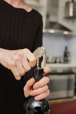 bar ware: Opening a wine bottle with corkscrew in a kitchen