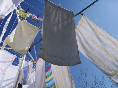 dry cleaned: clothes hanging on a clothes drying rack on a sunny day Stock Photo
