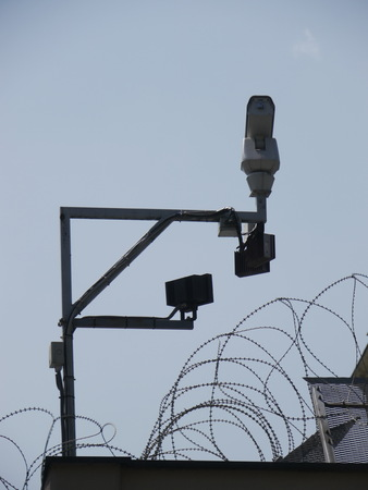 barbed wire fence: surveillance camera behind a fence with barbed wire. Focus on the fence.