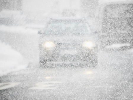 driving conditions: Slippery driving conditions in winter, snow is falling limited sight in traffic.