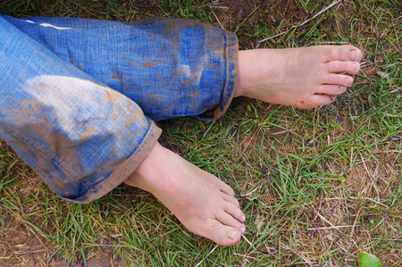 dirty feet: Close up view of the lower legs of a young woman with bare feet and muddy jeans over grass