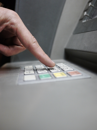 automat: a finger is typing at a money automat Stock Photo