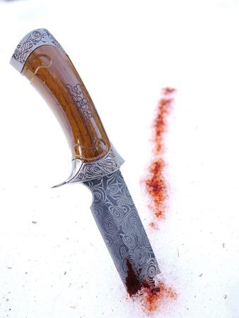 rotes Blut auf weißem Schnee und einem Messer Standard-Bild