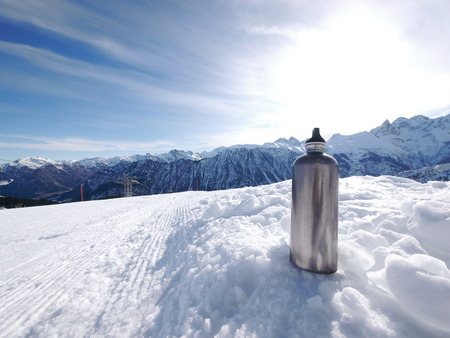 thermos: a silver thermos flask on a slope