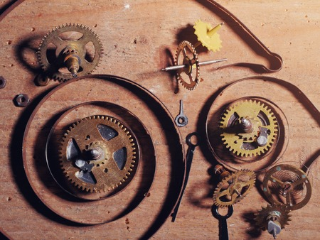 timepiece: Various clock parts laid on a rustic wood background, viewed from above