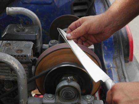 sharpening process: Vintage knife grinder grinding long knife Stock Photo