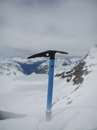 ice axe: Close-up of Ice axe in snow with mountains on background