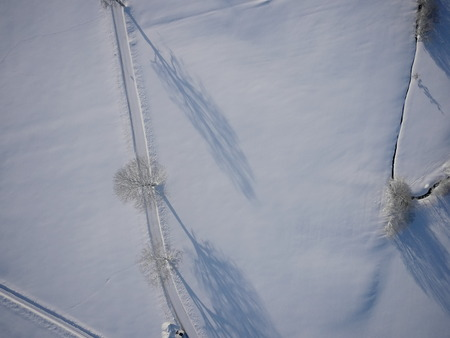 snowy field: aerial view over snowy field and road