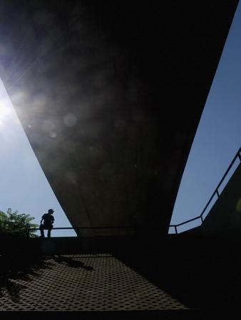 from below: View on bridge from below in sunlight. Man sitting on railing