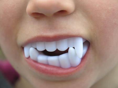 vampire teeth: White Plastic Vampire Teeth dracula plastic children teeth Stock Photo
