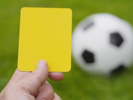 arbitro: Árbitro del fútbol a mano con tarjeta amarilla