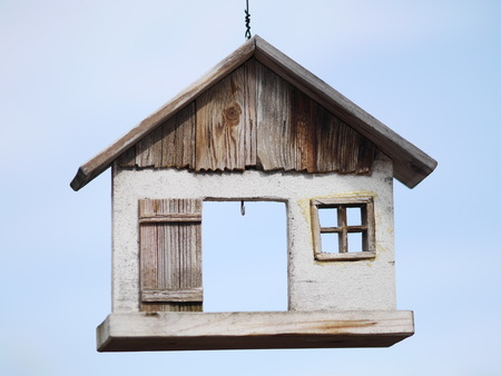 Quaint hanging sign of a wooden hut with an open doorway and small window suspended on a chain against a blue sky