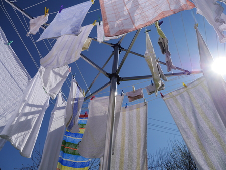 dry cleaner: clothes hanging on a clothes drying rack on a sunny day Stock Photo