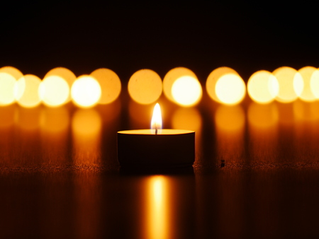 One candle flame at night with bokeh