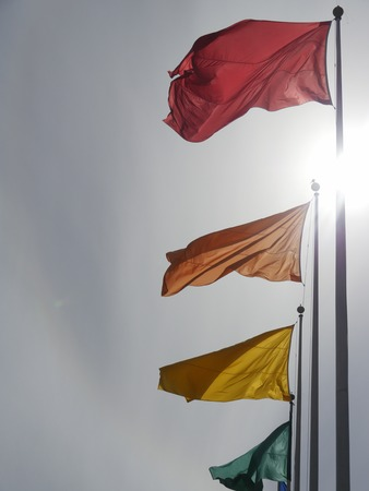 from below: View on flags of different colors waving against of sunny clear sky. From below Stock Photo