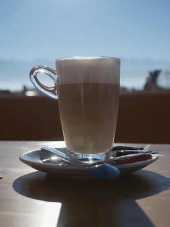 to get warm: Hot drink in glass on saucer with spoon and sugar. Sunny day.  Stock Photo