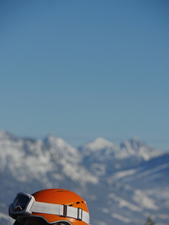unrecognizable person: Close-up of unrecognizable person wearing orange protective helmet and snowmask.Unfocused mountains on background.Copy space Stock Photo