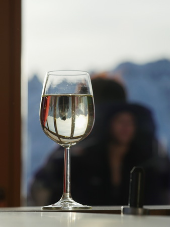 incognito: Glass of white wine with mirror reflection against of somebody sitting on background.