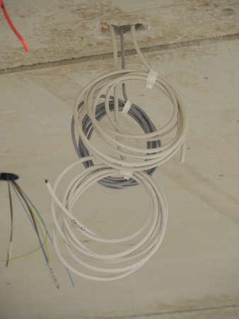 from below: Two grey rolled wires sticking out of cement ceiling. From below Stock Photo