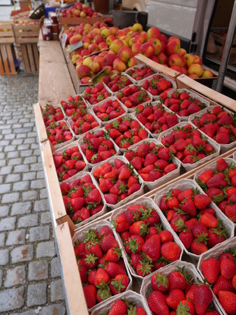 Bright red strawberry and apples at marketplace. Stock Photo