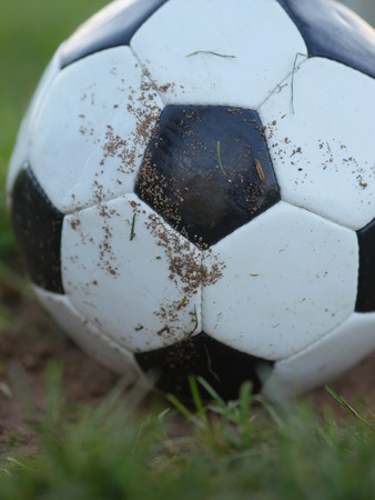 dirty football: old, dirty football laying on field