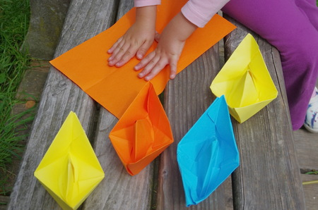colorful water surface: child playing with paper boats Stock Photo