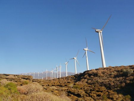 kinetic energy: Wind farm in Tenerife, Spain with a long line of wind turbines on the crest of a hill for converting the kinetic energy of the wind to sustainable electricity using natural resources