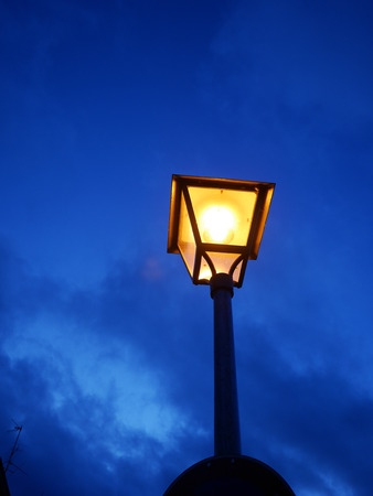 street lamp: Illuminated street lamp against of evening cloudy sky. Copy space.