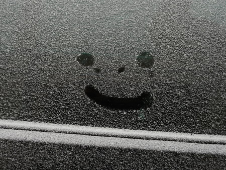 smiley face car: Car covered snow with drawn smiley in the surface of side window, texture of wet white snow on the car, happy cheerful image, holiday concept, winter outdoor close-up